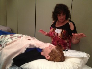 Roseanne is using Healing Hands in Motion to remove energetic debris in client's field.